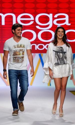 31.jul.2013 - Os atores Bruno Gissoni e Fernanda Paes Leme entram sorrindo ao final do desfile no evento do Mega Polo Moda