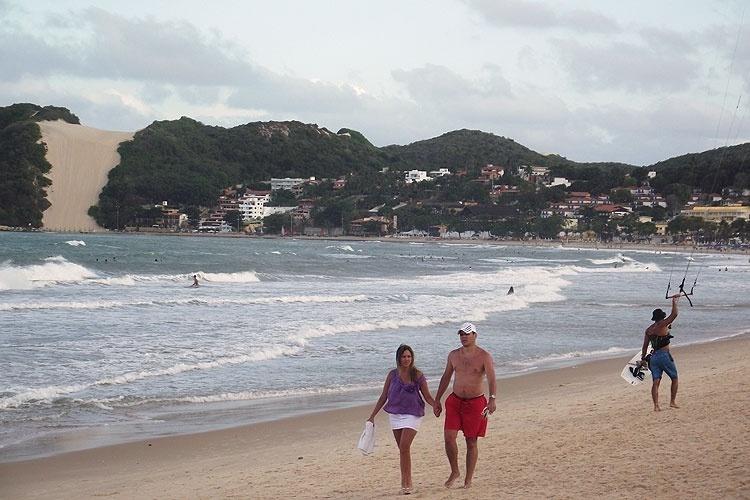 Casal e kitesurfista na orla de Ponta Negra; ao fundo, à esquerda, o Morro do Careca