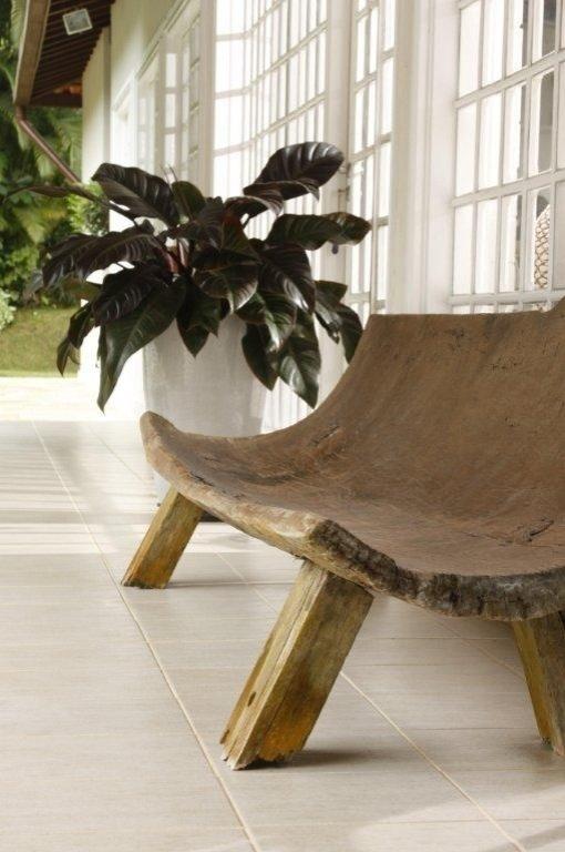 O formato inusitado do banco curvo de madeira cria um quadro encantador na varanda. A Casa Iporanga teve o projeto de reforma assinado pela designer de interiores Marília de Campos Veiga