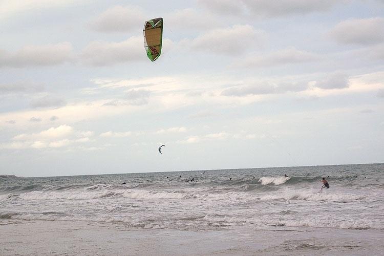 Surfistas e kitesurfistas convivem nas águas claras da praia de Ponta Negra, em Natal