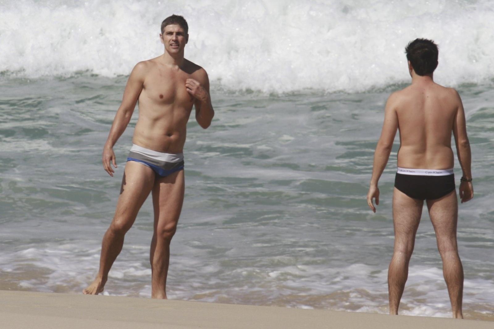 2.ago.2013 - Acompanhado de um amigo, o ator Reynaldo Gianecchini mergulha na praia da Reserva, na zona oeste do Rio