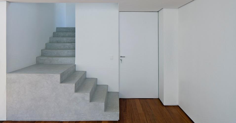 Com três níveis de piso, as escadas de acesso têm acabamento em cimento queimado e não possuem corrimãos ou guarda-corpos. No piso da Casa dos Pástio projetada pelo escritório AR Arquitetos, em São Paulo, o assoalho é de perobinha