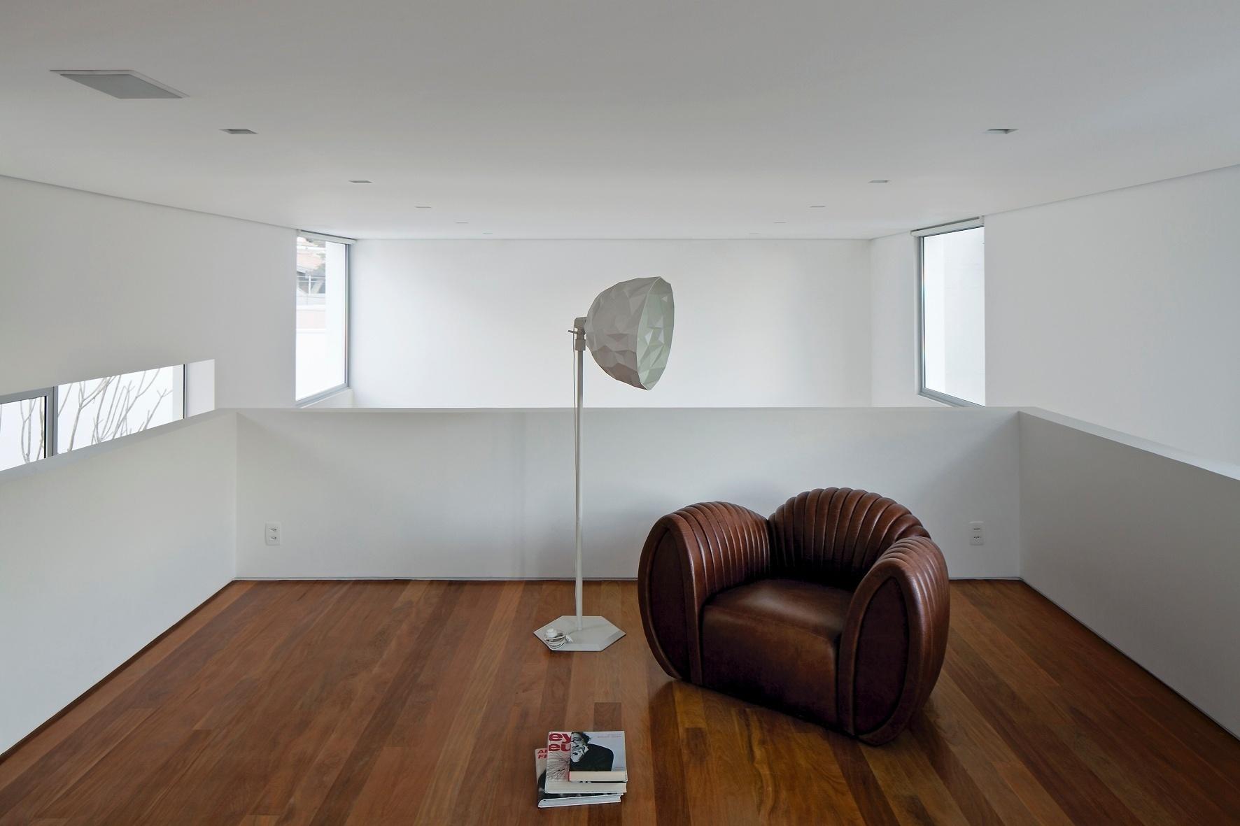 No mezanino, pavimento intermediário e amplo da Casa dos Pátios, há uma sala de leitura com 30 m². O espaço é decorado espartanamente por uma poltrona Shell, do Estudio Bola, e uma luminária de piso Rock, da Lumini. O projeto arquitetônico é do escritório AR Arquitetos