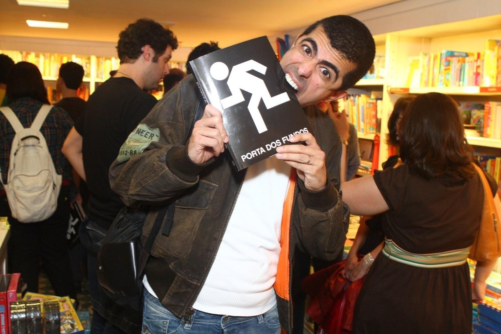 8.ago.2013 - O ator Marcius Melhem faz graça com o livro do