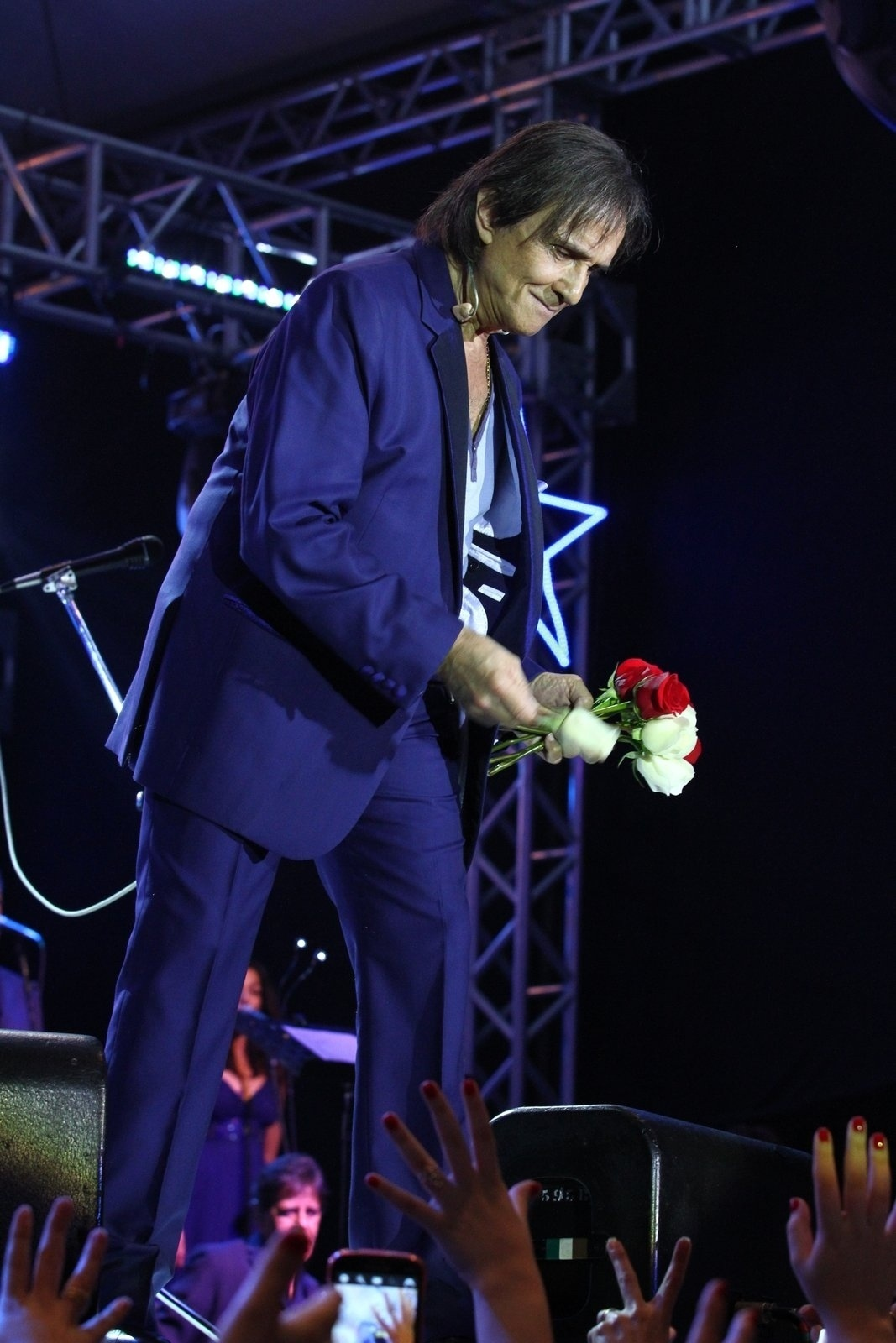 9.ago.2013 - Roberto Carlos beija e distribui suas tradicionais rosas ao fim da apresentação no Forte de Copacabana, Rio de Janeiro. O Rei cantou seus maiores sucessos acompanhado de orquestra e coral. O show faz parte de uma série de cinco apresentações na capital carioca