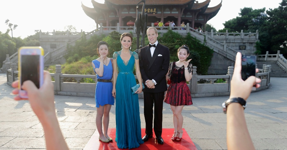 13.ago.2013 - Visitantes posam com figuras de cera do príncipe William e Kate Middleton em frente ao  Yellow Crane Tower, em Wuhan