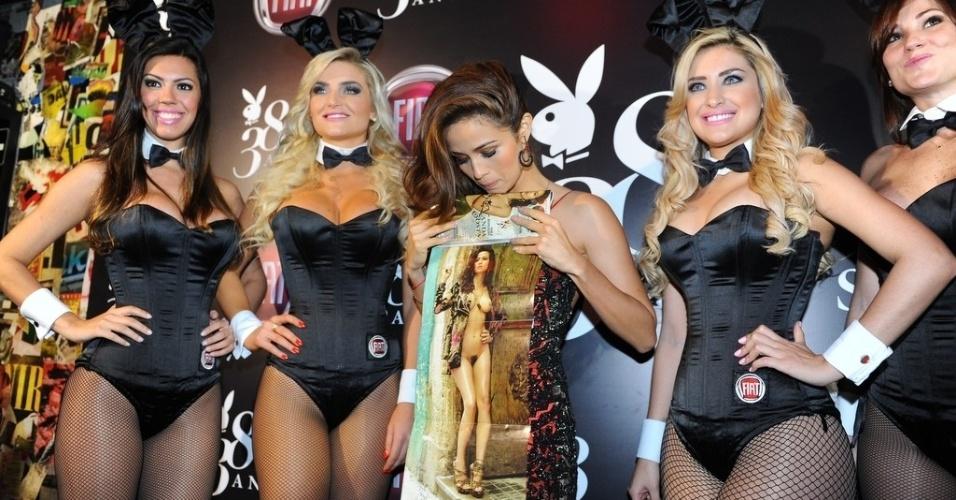 """13.ago.2013 - Ao lado de coelhinhas, Nanda Costa exibe pôster de seu ensaio nu para a """"Playboy"""" de agosto. A festa de lançamento da edição, que também comemora o aniversário da revista, aconteceu em um bar de São Paulo"""