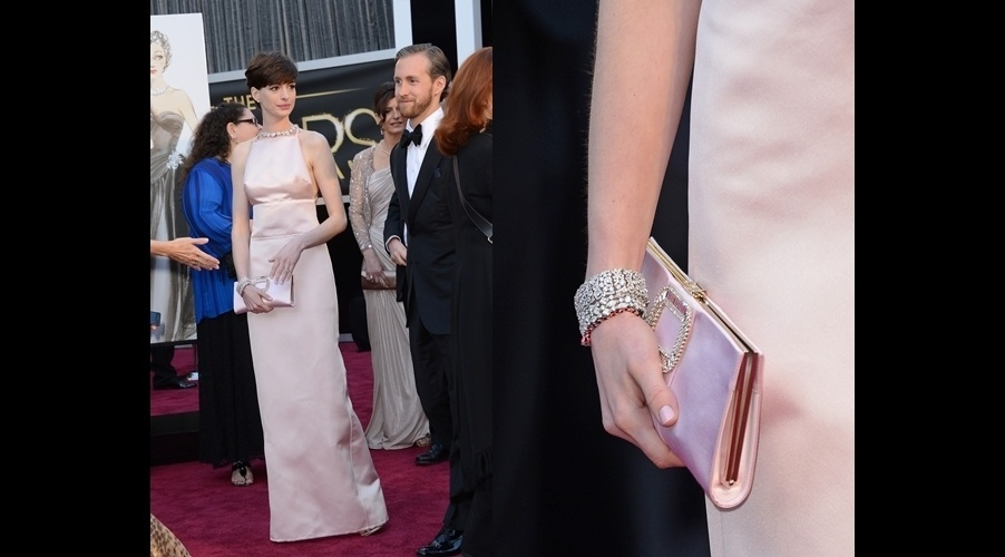 Anne Hathaway em um look inteiramente Prada usa uma clutch de cetim que combina com seu vestido e joias
