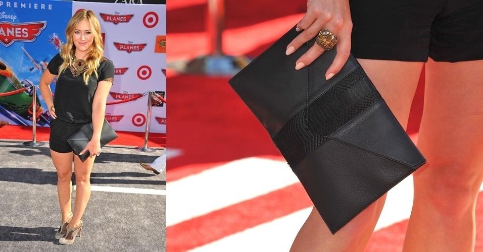 Hilary Duff escolheu uma clutch envelope da marca Donattiene que completou seu look todo preto