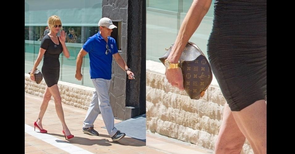 Melanie Griffith sai com sua clutch Louis Vuitton, pequena e discreta, combinando com o vestidinho preto