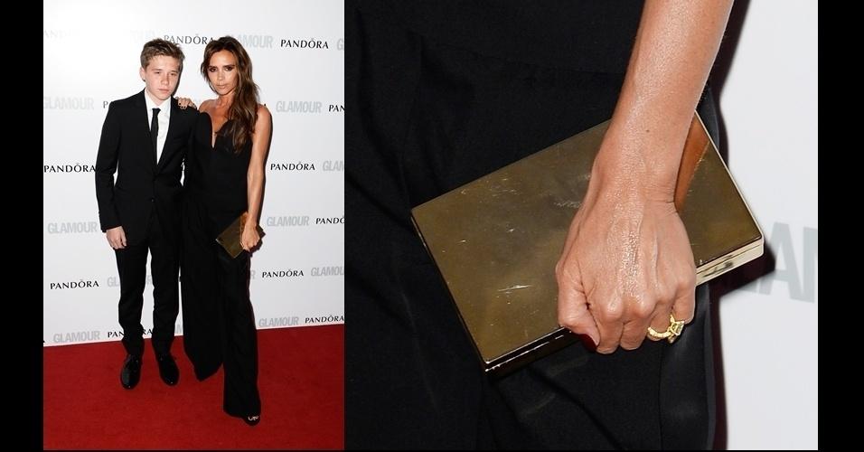 Victoria Beckham posa ao lado de seu filho mais velho usando uma clutch metalizada dourada de sua própria marca