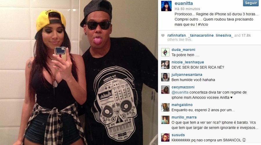 25.ago.2013 - Depois de ter sido roubada, Anitta mostra novo celular ao lado de amigo