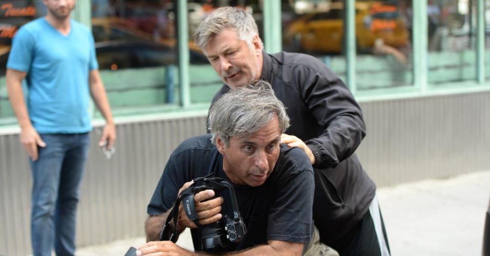 27.ago.2013 - Alec Baldwin empurra e imobiliza um paparazzo que o seguia enquanto ele passeava com a mulher, Hilaria, que deu à luz há menos de uma semana, em rua de Nova York