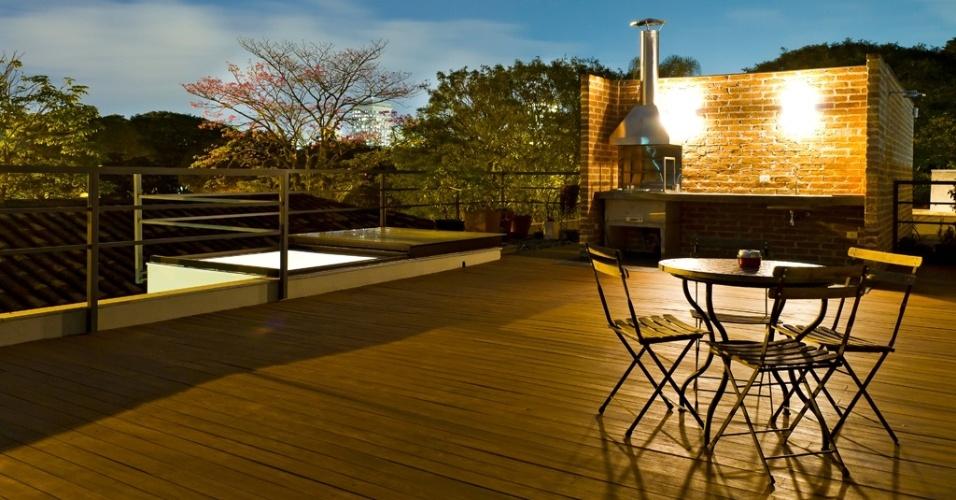 A área do solarium apresenta uma atmosfera agradável nas noites de céu límpido em São Paulo. Com deck de madeira e churrasqueira, o lugar é ideal para o lazer ao ar livre. A Casa Urbana foi projetada pela arquiteta Paula Bittar