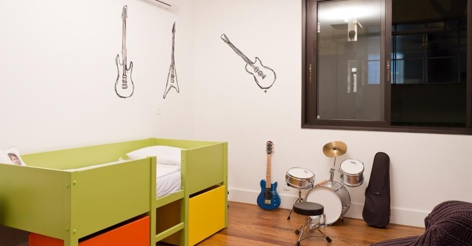 Apaixonado por música, um dos filhos do casal reservou um espaço de seu quarto para bateria, guitarra e violão, instrumentos que também estão desenhados na parede. A cama alta tem dois gavetões coloridos na parte inferior. O projeto da Casa Urbana é da arquiteta Paula Bittar