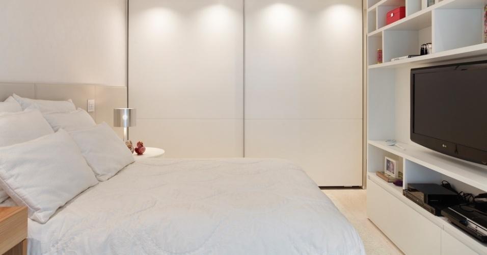 No projeto da arquiteta Izabella Lessa, as portas brancas do armário distinguem-se pelo discreto friso. Os pontos de luz no forro, planejados por Maneco Quinderé, criam volumetria no ambiente que teve o piso, em travertino bruto, protegido pelo confortável tapete Avanti, também de cor clara