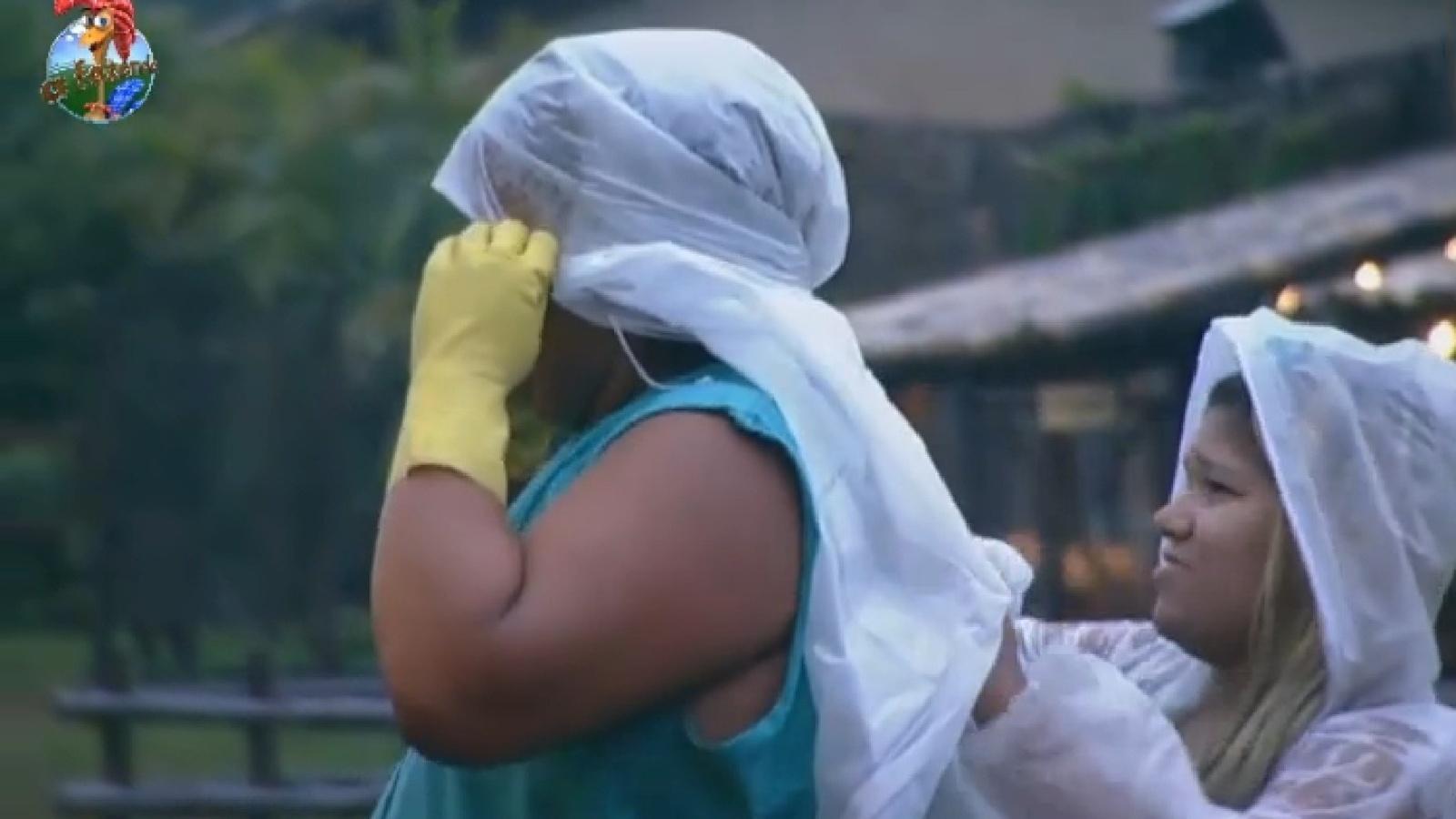 17.set.2013 - Mulher Filé ajuda Gominho a vestir capa em manhã chuvosa