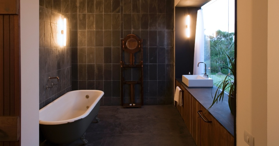 Na ampla sala de banho, optou-se pela ardósia preta como revestimento das paredes e pelo piso de cimento queimado. A casa no sítio Santo Antônio, em São Pedro (SP), foi projetada pelo arquiteto Eduardo de Oliveira Rosa
