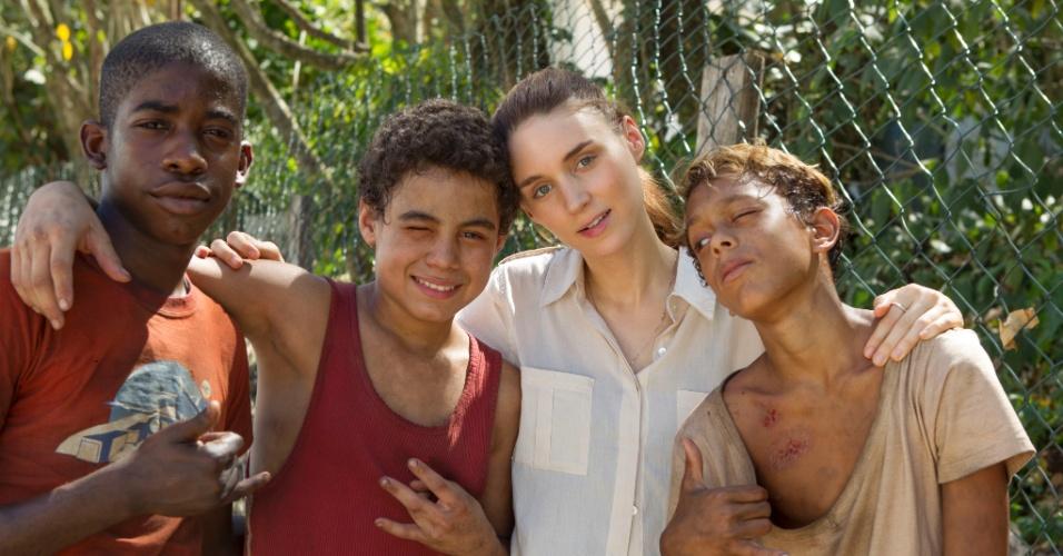 """Rooney Mara com meninos que interpretam Raphael, Gardo e Rato no filme """"Trash"""".  O longa é um thriller contemporâneo que acompanha três garotos que vivem num lixão"""