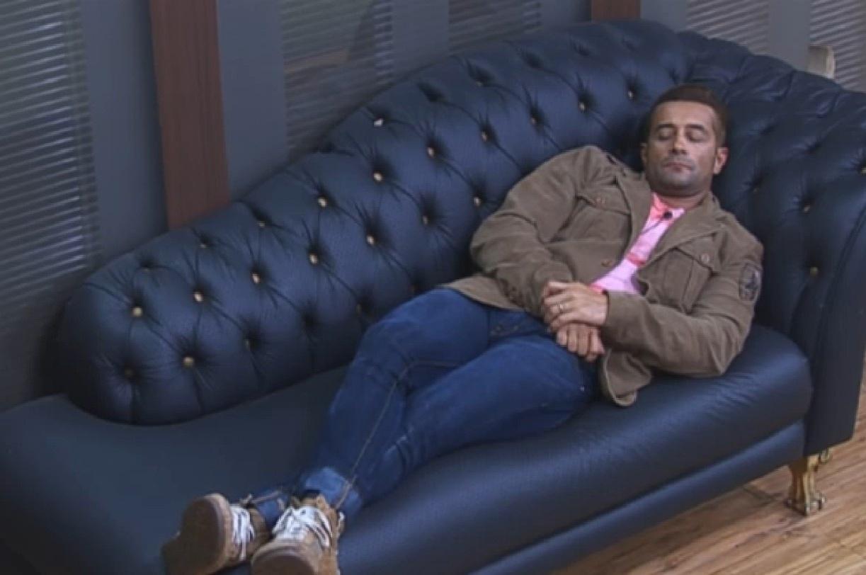 23.set.2013 - Marcos Oliver cochila no sofá da sala