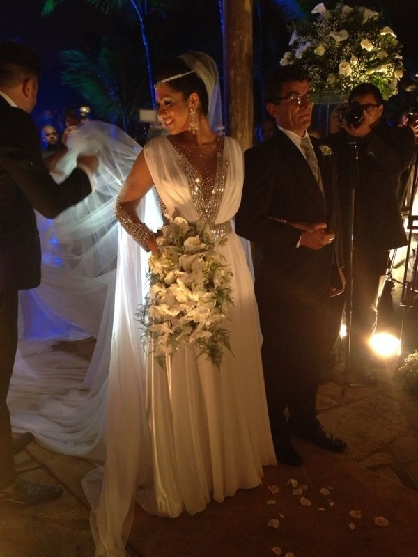 Depois de problemas com o estilista, vestido de noiva de Mulher Moranguinho conta com decote e cristais prateados. Ellen chegou ao casamento em um Jaguar preto, não em uma carruagem, como queria inicialmente. Nas mãos, um buquê de orquídeas brancas