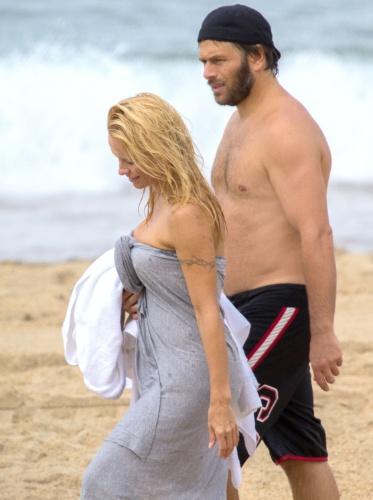 2.ou.2013 - De topless, Pamela Anderson curte praia em Biarritz, na França, com o namorado, o produtor Rick Solomon.