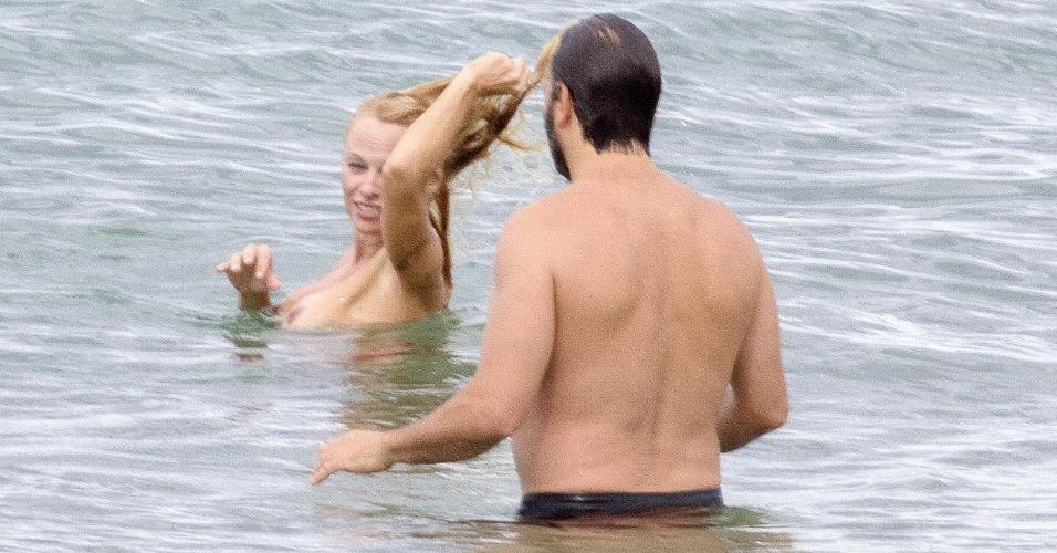 2.ou.2013 - De topless, Pamela Anderson curte praia em Biarritz, na França, com o namorado, Rick Solomon.