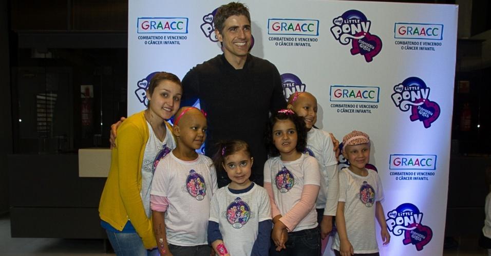 3.out.2013 - O ator Reynaldo Giannechini posa ao lado de crianças atendidas pelo GRAACC no lançamento do filme