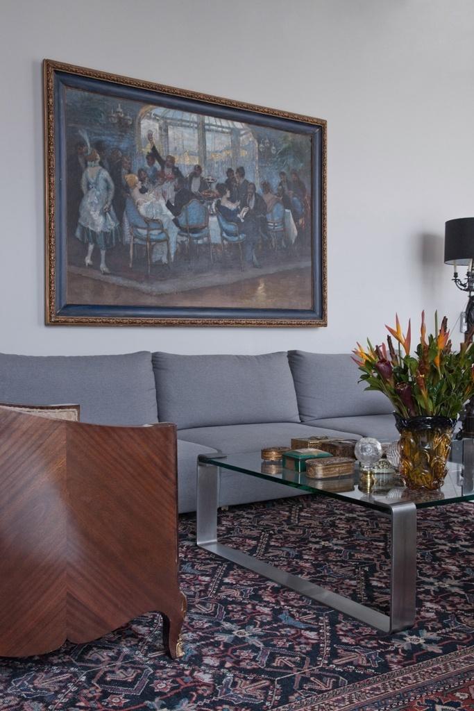 Com projeto de reforma e decoração do designer de interiores Oscar Mikail, o apartamento com vista para a Paulista exibe ambientes elegantes compostos com base na equilibrada mescla de estilos. É o caso do home theater que conta com um quadro veneziano de 1850, um sofá de linho cinza - da Casa Matriz -, um par de poltronas de mogno anos 1940 e um tapete persa do século 19, além da mesa de aço e vidro da Staten. Sobre ela, coleção de caixas francesas e vaso de Murano