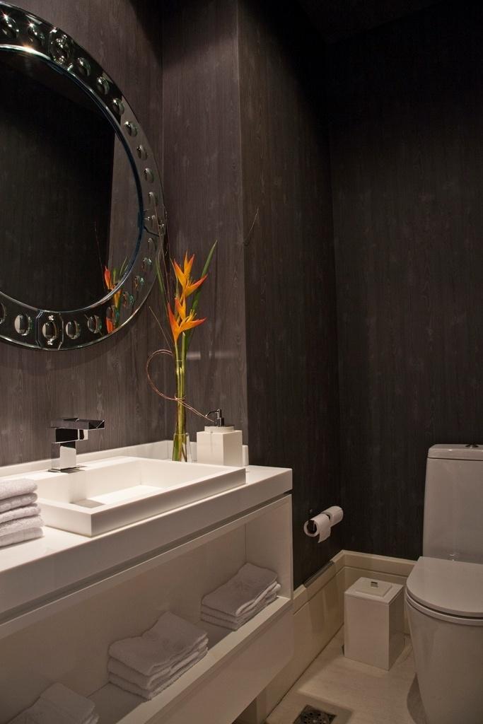 No lavabo, as paredes foram revestidas por papel que imita madeira ebanizada, da Coquelicots. O espelho é uma releitura das peças de Murano. Ainda no espaço, as louças Deca foram combinadas aos metais e à cuba da Interbagno. O projeto de reforma e interiores é do designer de interiores Oscar Mikail