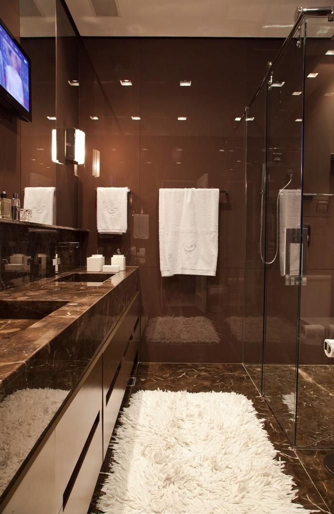 O banheiro do morador possui visual bem masculino, dado pela cor escolhida: marrom. As paredes são revestidas por vidros no matiz, que sem mantém no piso e na bancada, em mármore marrom Imperial, da Marmogrini. O projeto de reforma e interiores é do designer de interiores Oscar Mikail