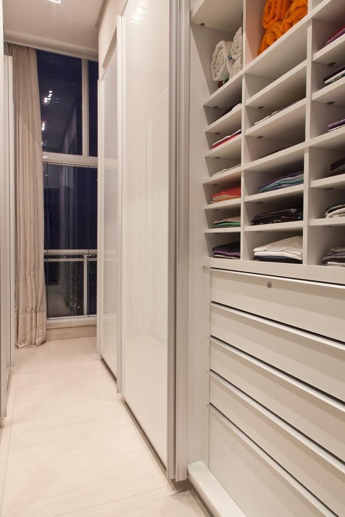 O projeto de reforma deste apartamento, assinado pelo designer de interiores Oscar Mikail, incluiu a instalação de um closet na suíte do proprietário. Em laminado branco, o quarto de vestir possui portas com vidro e espelho, prateleiras e gavetas, além de uma janela, que favorece a entrada de luz e ventilação naturais