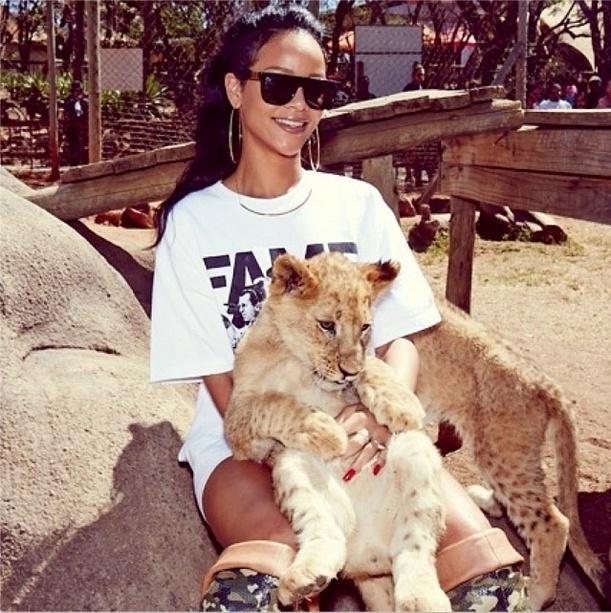 14.out.2013 - Rihanna sorri ao posar para foto com um filhote no colo no Lion Park em Johannesburgo