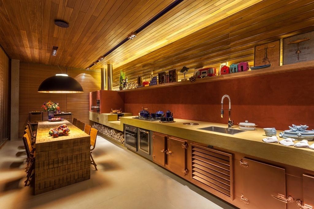 Casa Cor MG - 2013: A decoradora Denise Vilela assina o Atelier Gourmand. Inspirado nas cozinhas das fazendas do interior, a área de cocção conta também com forno de pizza, churrasqueira e fogão à lenha. Nos revestimentos, o cimento queimados amarelo (bancada) e vermelho (parte da parede) foi combinado ao painel de madeira que sobe do terço superior da parede e recobre o forro