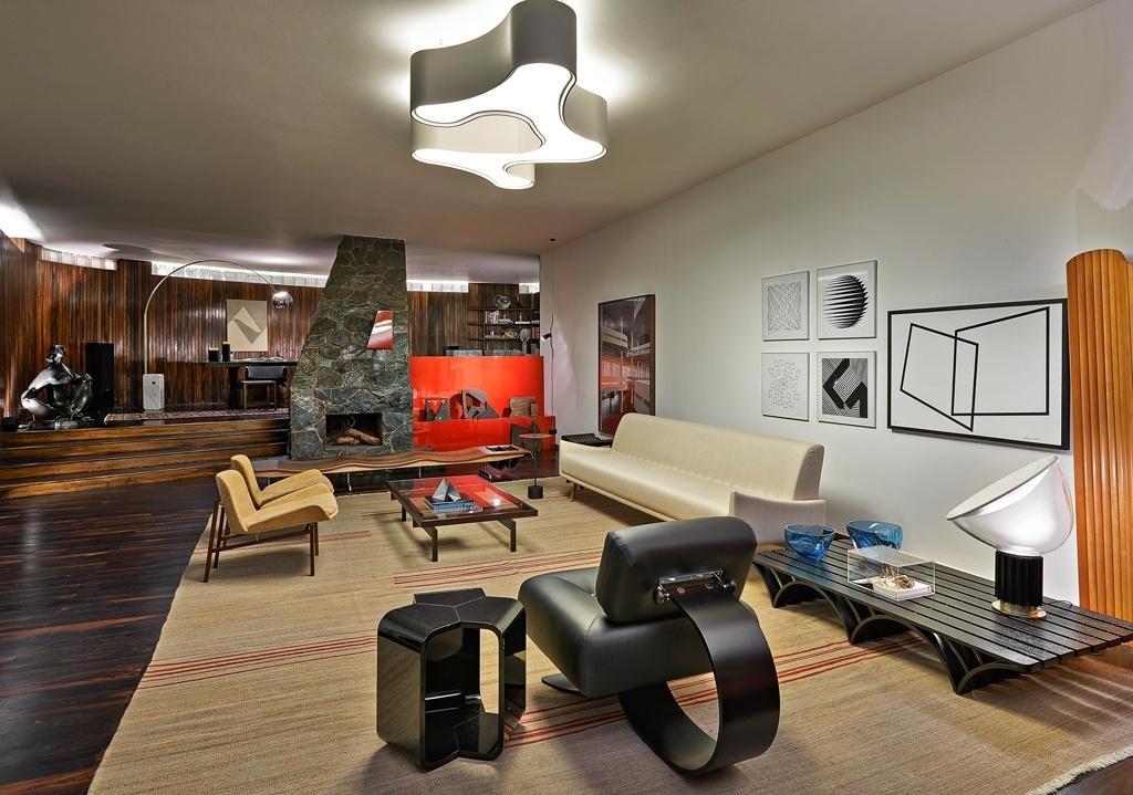 Casa Cor MG - 2013: Peças esculturais - como a cadeira Easy, desenhada por Oscar Niemeyer (em primeiro plano, de costas), ou a luminária Taccia (à dir.), criada por Achille e Pier Giacomo Castiglioni, - determinam a ambientação do Living, assinado pela designer de interiores Lena Pinheiro