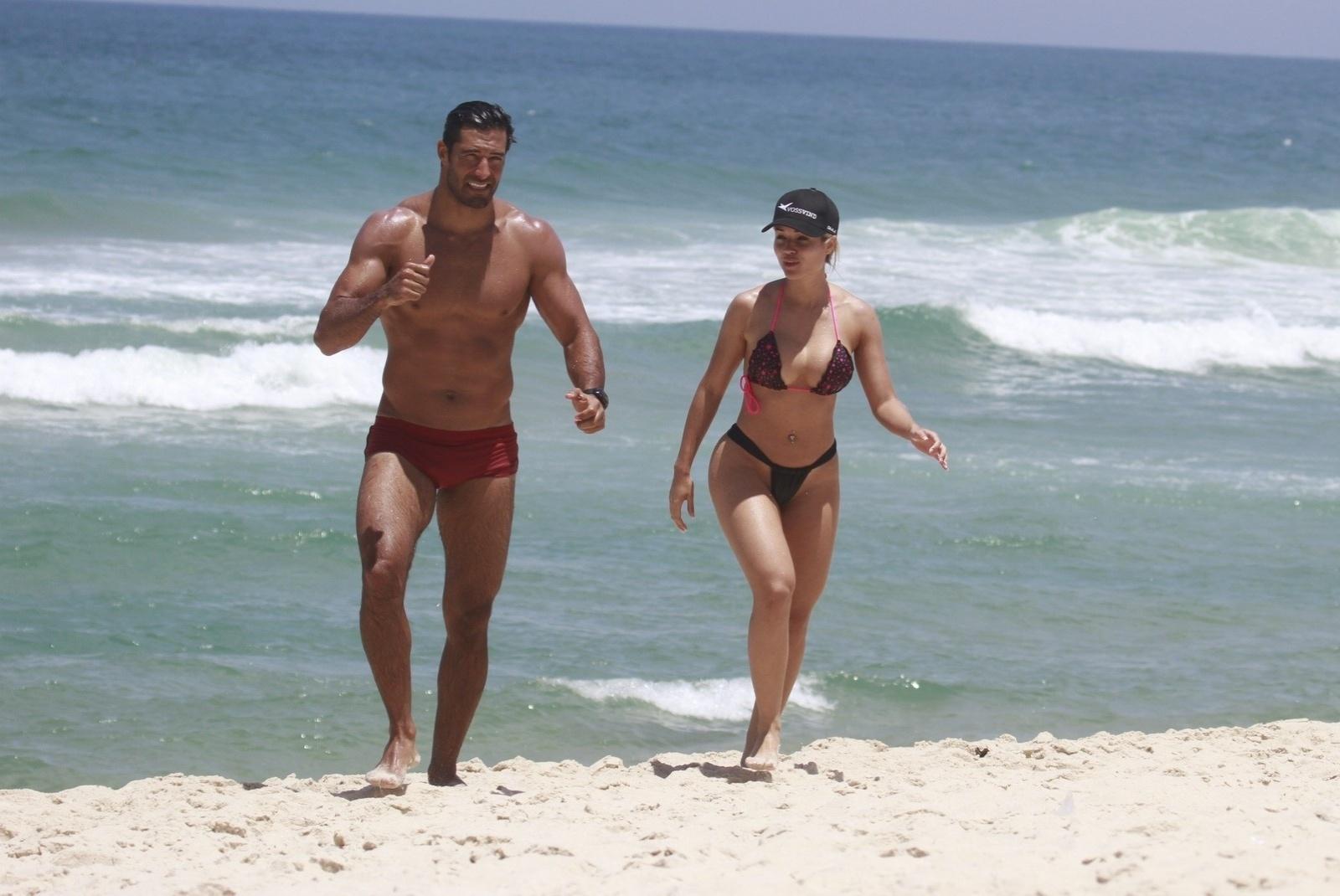 24.out.2013 - Beto Malfacini e Aryane Steinkopf aproveitaram a quinta de calor do Rio para curtirem praia em Grumari, zona oeste da cidade. O casal se conheceu durante participação na última edição do reality
