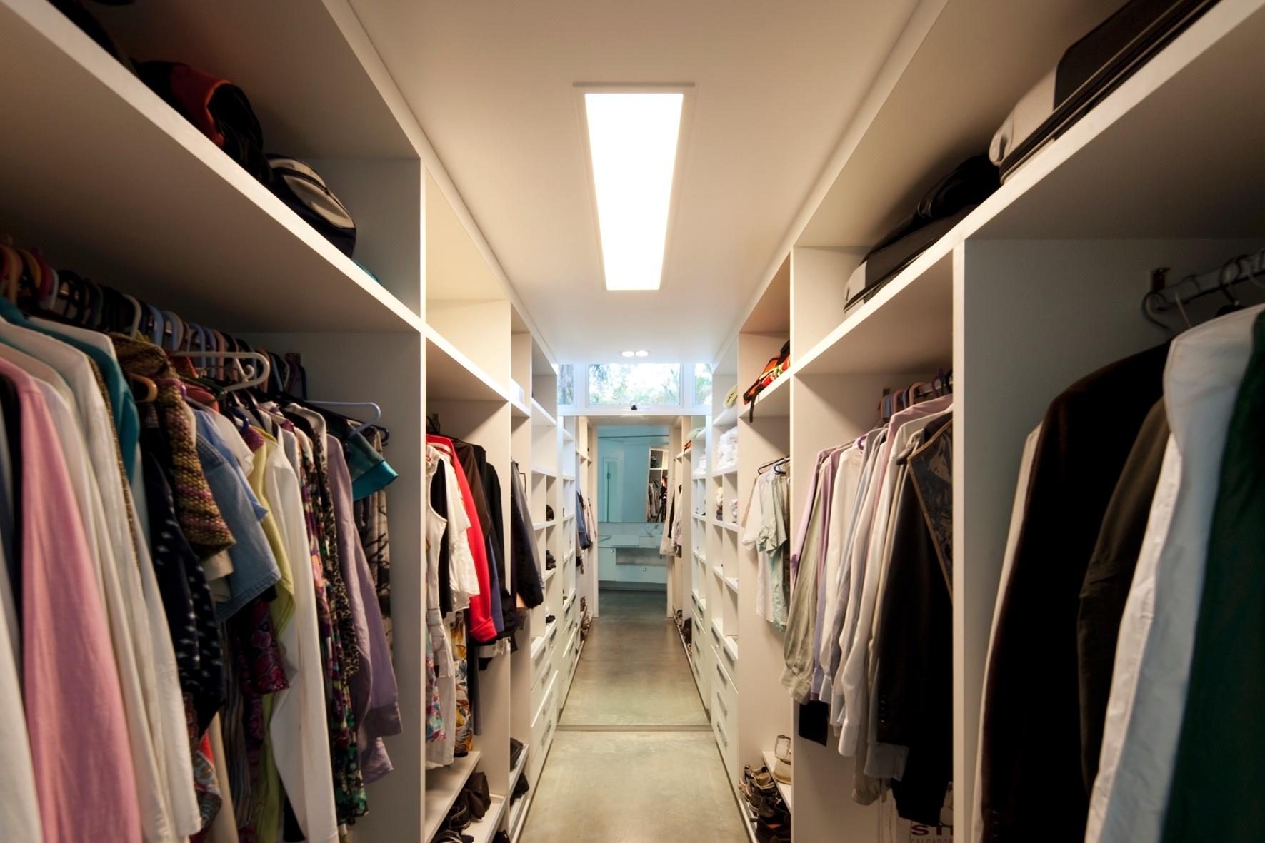 generoso closet da suíte do casal possui armários distribuídos em  #AF1C24 1771 1181