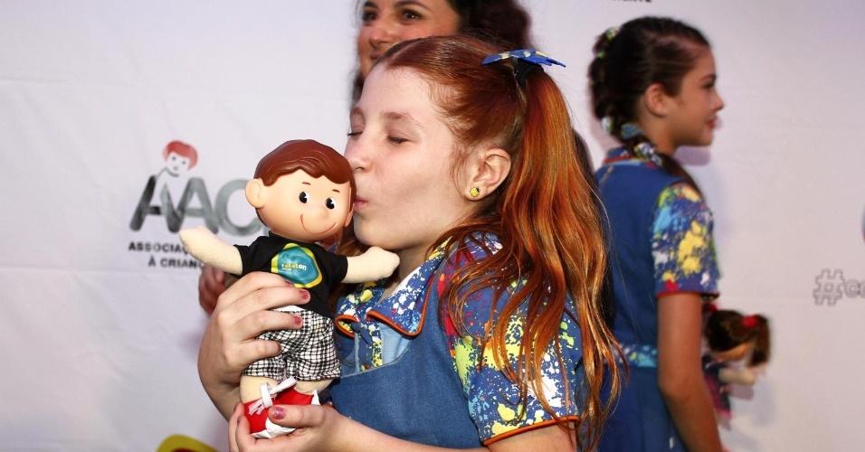 """26.out.2013 - A atriz Giulia Garcia, intérprete de Ana em """"Chiquititas"""", beija boneco oficial da campanha"""