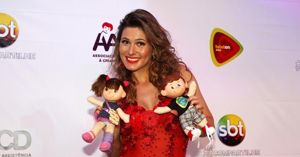 26.out.2013 - De vestido vermelho, Lívia Andrade posa com bonecos oficiais da campanha, nos bastidores do programa