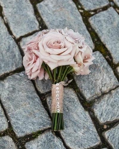 Buquê de flores rosas com haste amarrada por um voal rosa decorado com strass