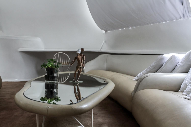 No living, os sofás também são parte do corpo da Casa Bola, ligados à estrutura principal da construção. O estofamento é feito com couro claro e, no chão, o tapete é marrom escuro, criando um contraste às superfícies brilhantes e quase totalmente brancas. A residência é assinada pelo arquiteto Eduardo Longo