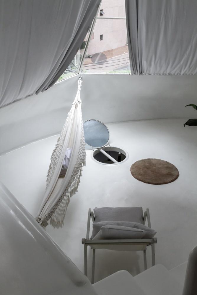 No terraço da Casa Bola, localizado no quarto pavimento, uma janela do tipo escotilha leva luz a um dos cômodos sociais localizados no piso abaixo: cozinha, sala de jantar e banheiro. A residência esférica estruturada em ferrocimento e localizada em São Paulo foi assinada pelo arquiteto Eduardo Longo