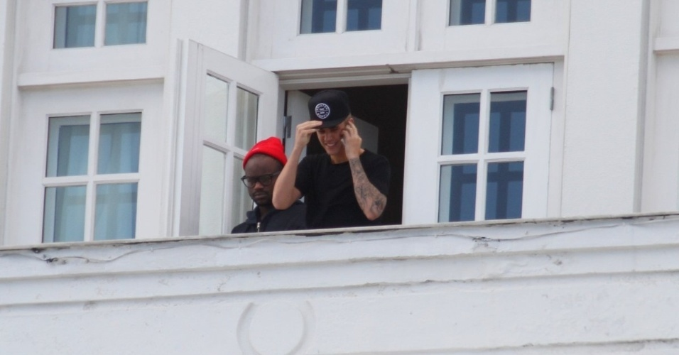 1.nov.2013 - Sem casaco e com outro boné, Justin Bieber volta para a sacada do Copacabana Palace falando no celular