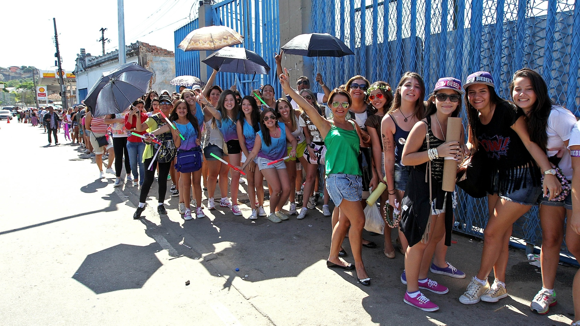 3.nov.2013 - Para se proteger do calor, fãs de Justin Bieber usam sombrinha para aguardar a abertura dos portões para assistir o último show do cantor no Rio de Janeiro
