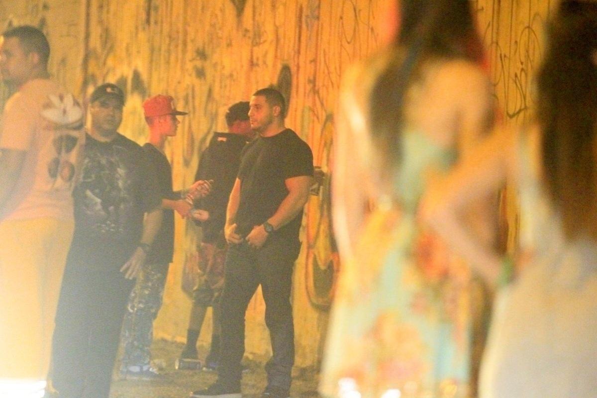 5.nov.2013 - Escoltado por seguranças, Justin Bieber grafita muro do bairro de São Conrado, no Rio de Janeiro, durante a madrugada. O cantor e sua equipe foram para o local por volta das 3h. De acordo com a agência de fotografias AgNews, os fotógrafos presentes no local foram agredidos pelos seguranças de Bieber e a polícia chegou a ser chamada. O astro teen ficou grafitando por cerca de três horas e atendeu a fãs