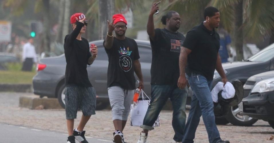 5.nov.2013 - Justin Bieber e sua equipe mostram o dedo do meio para paparazzi ao ver que estão sendo fotografados andando pela orla da praia da Barra da Tijuca