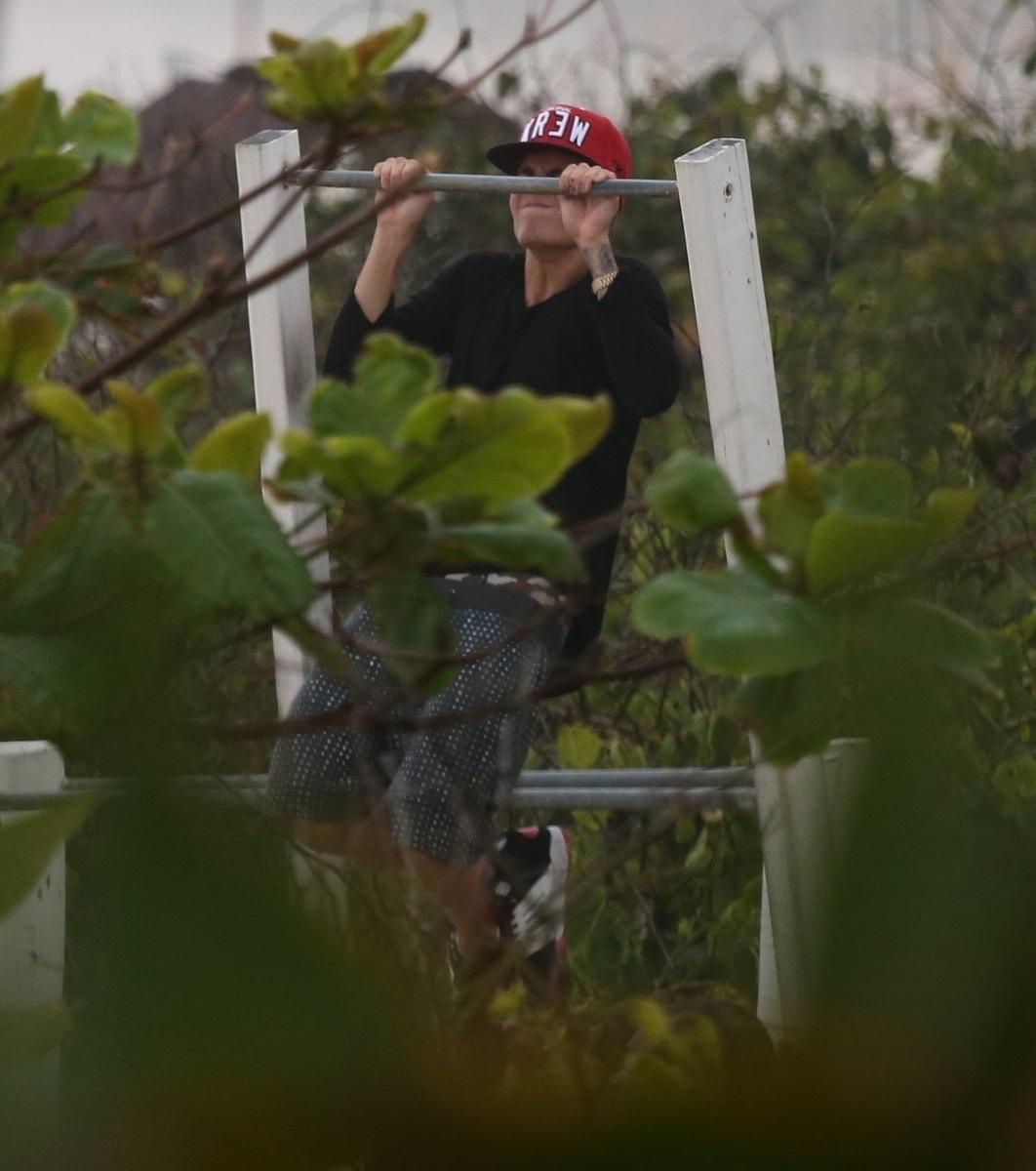 5.nov.2013 - Justin Bieber faz exercícios em uma barra que fica na praia da Barra da Tijuca. O cantor estava acompanhado de amigos e seguranças e tentou passar despercebido, usando óculos e boné