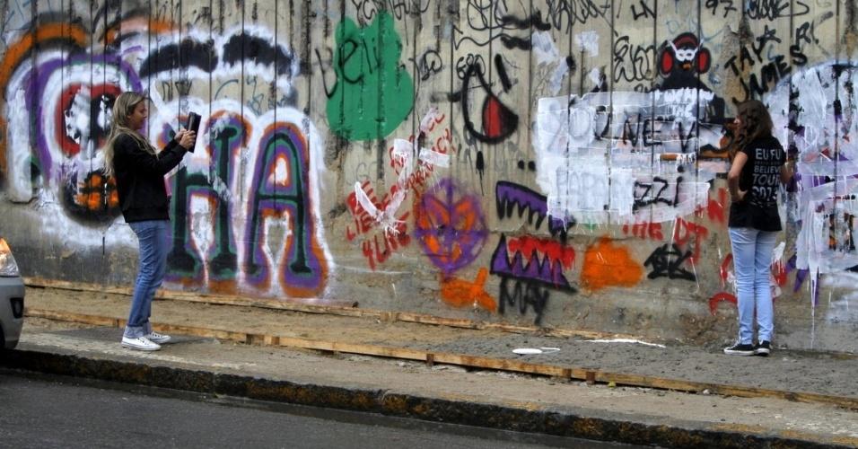 5.nov.2013 - Fãs foram ao local tirar fotos com os desenhos, mas ficaram inconformados com os grafites cobertos e brigaram com os fotógrafos que fizeram o estrago