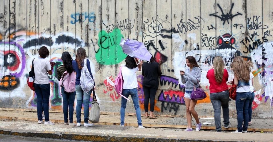 5.nov.2013 - Fãs tiram fotos no muro que foi grafitado por Bieber durante a madrugada