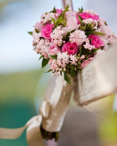 Buquê com flores em tons de rosa e haste envolta por fita de cetim com laço no final